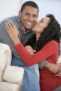 Couple in living room kissing and smiling