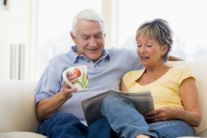 Couple in living room reading newspaper with coffee smiling