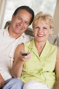 Couple in living room using remote control smiling