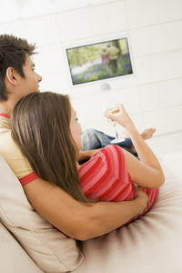 Couple in living room watching television and drinking white wine