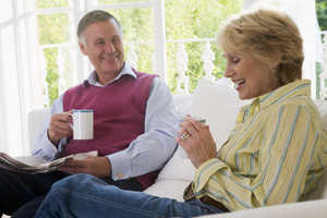 Couple in living room with coffee and newspaper smiling