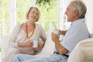 Couple in living room with coffee smiling