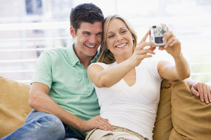 Couple in living room with digital camera smiling
