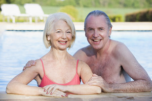 Couple in outdoor pool smiling
