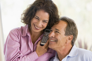 Couple indoors using telephone smiling