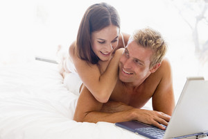 Couple lying in bed with laptop smiling
