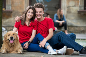 Couple of teenagers in love posing with a dog