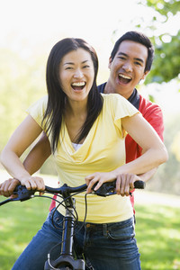 Couple on a bike outdoors smiling