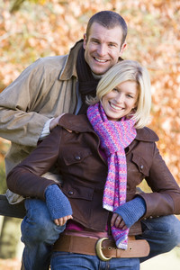 Couple on autumn walk sitting on fence