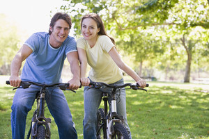 Couple on bikes outdoors smiling