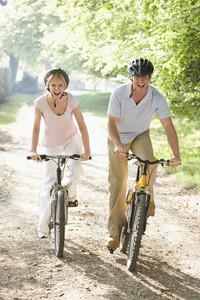 Couple on bikes outdoors smiling