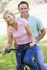 Couple on one bike outdoors smiling