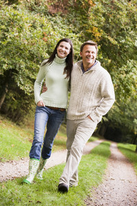 Couple on woodland walk along woodland path in autumn