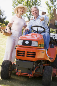 Couple outdoors with tools and lawnmower pointing and smiling
