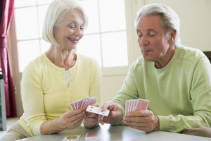 Couple playing cards in living room smiling