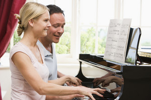 Couple playing piano and smiling