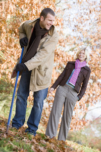 Couple raking autumn leaves in garden