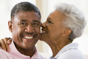 Couple relaxing indoors kissing and smiling
