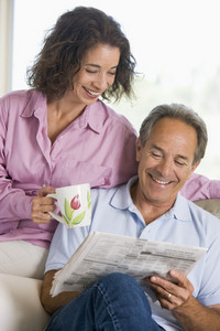Couple relaxing with a newspaper smiling
