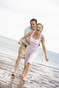 Couple running at the beach smiling