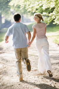 Couple running outdoors holding hands