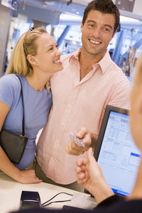 Couple shopping in store with credit card