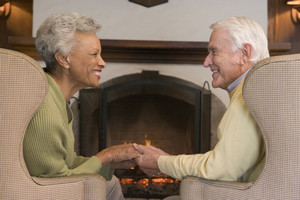 Couple sitting in living room by fireplace holding hands and smiling