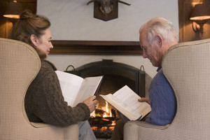 Couple sitting in living room by fireplace reading