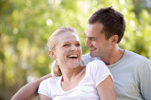 Couple sitting outdoors laughing