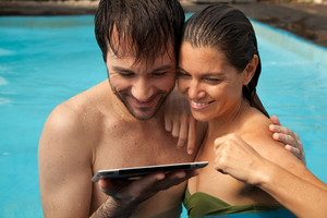 Couple using the tablet on the pool