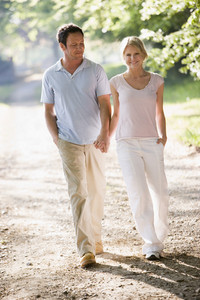 Couple walking outdoors holding hands and smiling