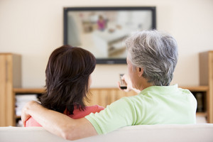 Couple watching television using remote control