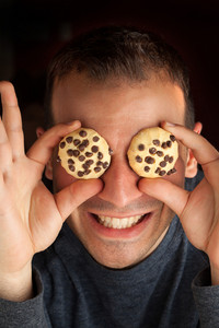 Crazy man holds cookies over his eyes.