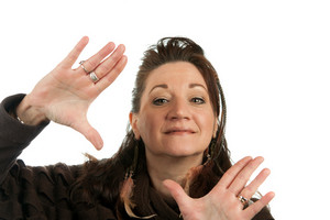 Creative woman with vision frames a scene with her hands isolated over a white background.