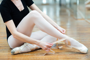 Cropped image of a ballerina dressing pointe shoes in ballet class