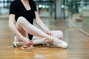 Cropped image of a ballerina tying pointe shoes in ballet class