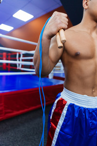 Cropped image of a boxer standing with skipping rope near boxing ring