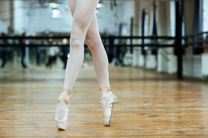 Cropped image of a female legs in pointe shoos standing on toes