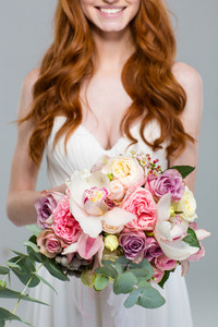 Cropped image of a happy redhead woman holding flowers