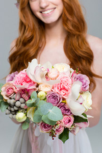 Cropped image of a smiling redhead woman holding flowers