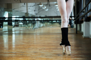 Cropped image of legs graceful ballerina in gym