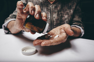 Cropped view of elderly woman taking prescription medicine from pill bottle. Senior female's hands pouring pills on her palm while sitting at a table.