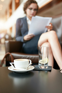 Cup of coffee and glass of water on cafe table with businesswoman sitting in background reading documents.