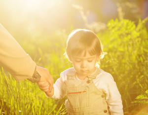 Cute adorable baby kid waoking in beautiful green grass holding mom's hand