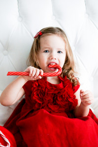 Cute Baby Girl In Red Fashionable Dress Sitting On White Bed And Eating Candy Cane