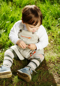 Cute baby sitting on grass in park