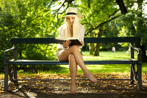 Cute blond sitting on a park bench and reading a book.