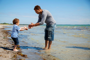Cute boy takes little steps towards his father to dip in the sea