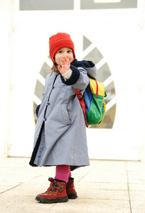Cute girl outdoor, going to kindergarten, saying bye