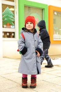 Cute girl outdoor, standing in front of preschool kindergarten